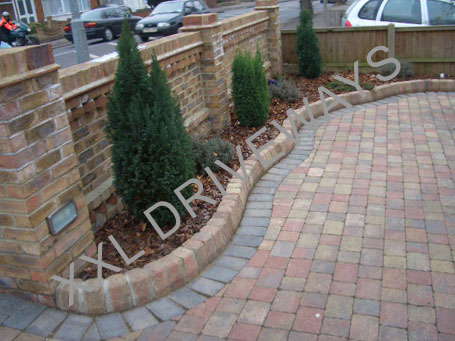 Block paved driveway with flower bed, brick wall surrounding property.