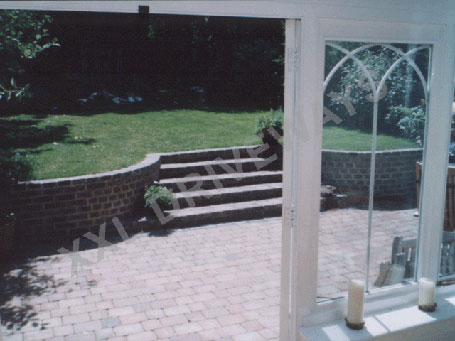 Block paved rear garden, brick wall including steps to new lawn.