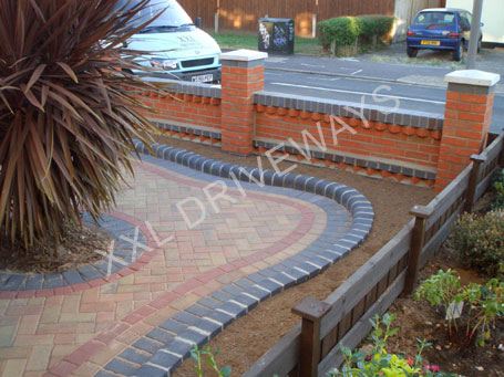 Block paved driveway, patio rear garden, brick front garden wall with flower bed.