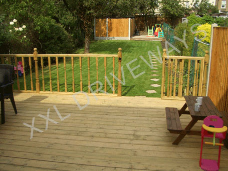 Wooden decking veranda, lawn, Indian stone patio and fence to rear garden.