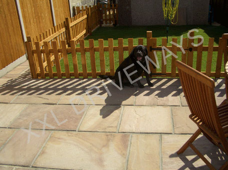 Indian stone patio and path, lawn with picket fence and gate, fence and back gate to rear garden.